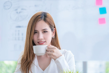 Asian business woman is checking the report while drinking coffee
