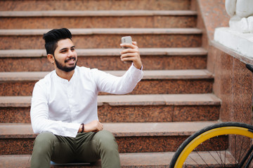 Excited young asian man sitting on stairs with bicycle, taking a selfie with mobile phone