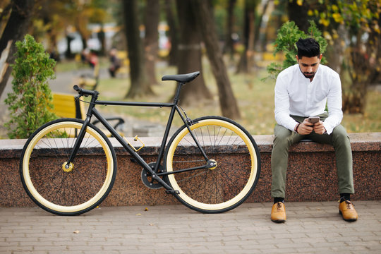 Lifestyle, transport, communication and people concept. Young indian man with bicycle and smartphone on city street