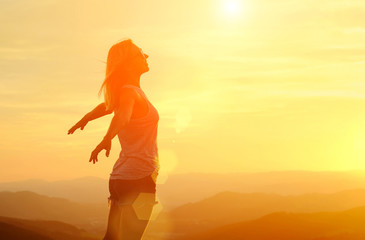 Happy woman with open arms stay on the peak of the mountain cliff edge under sunset light sky enjoying the success, freedom and bright future.