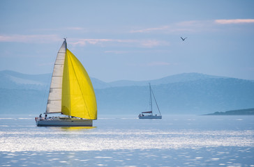 Sailing boat with yellow spinnaker sailing on calm sea