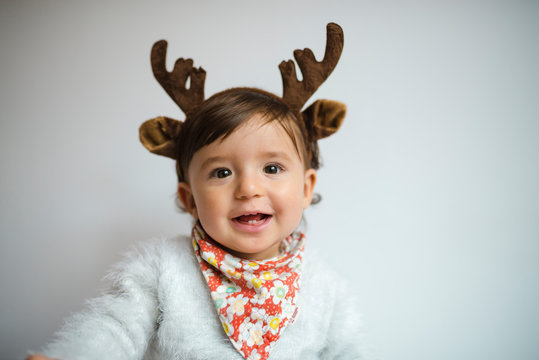 Portrait of laughing baby girl with reindeer antlers headband