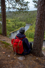 Finland, Oulanka National Park, woman with backpack sitting in pristine nature