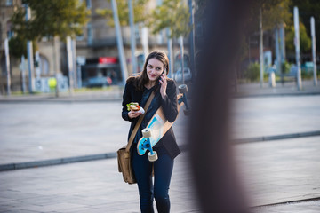 Young woman with longboard and snack in the city on the phone