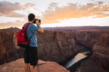 USA, Arizona, Colorado River, Horseshoe Bend, young man on viewpoint, photographing