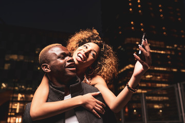 Happy young couple taking selfie at night in the city