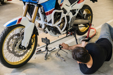 Man placing video camera next to motorcycle in workshop