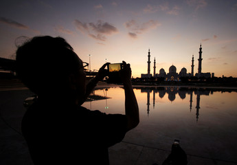 A visitor takes photos of Sheikh Zayed Mosque with their smart phone in Abu Dhabi