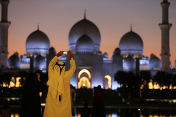 Visitors take photos of Sheikh Zayed Mosque with their smart phones in Abu Dhabi