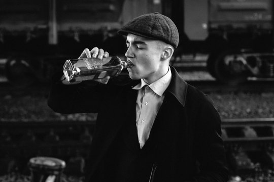 stylish gangster man drinking. posing on background of railway. england in 1920s theme. fashionable brutal confident guy. atmospheric  moments. space for text.black white photo