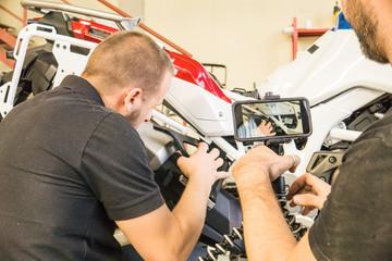 Mechanic working on motorcycle in workshop filmed by his partner