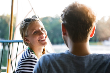 Young woman laughing at man at a lake next to sailing boat
