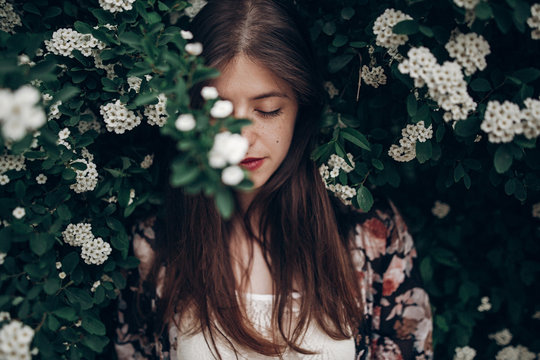 calm portrait of beautiful hipster woman in blooming bush with white flowers of spirea. boho girl sensual portrait in floral modern clothes in greenery. space for text