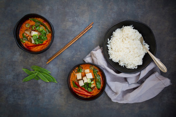 Two bowls of red Thai Curry with snow peas, carrots, bell pepper, spring onions and smoked tofu