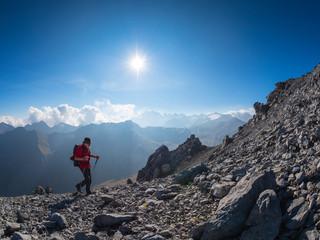 Border region Italy Switzerland, senior man hiking in mountain landscape at Piz Umbrail