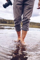 Sweden, Lapland, man with camera wading in water, partial view