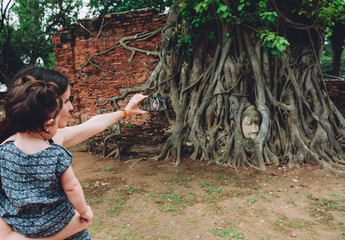 Thailand, Ayutthaya, Mother and daughter taking a photo of the Buddha head in between tree roots at Wat Mahathat
