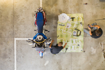Two men arranging items next to motorcycle in workshop