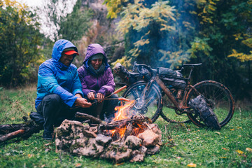 Laughing couple with with bmx bikes sitting at camp fire grilling sausages