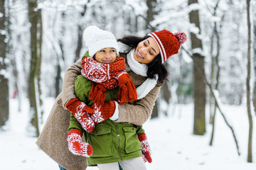attractive african american mother hugging cute preteen daughter in winter forest