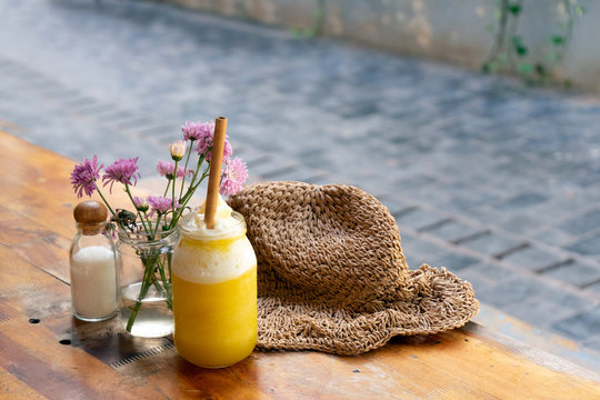 A jar of fresh yellow pineapple and mango smoothie with a bamboo straw on the table with a straw hat and a vase of pink flowers near it. Summer concept. No more plastic straw concept