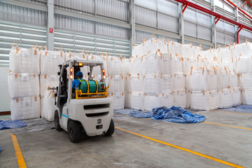 Forklift is handling jumbo bags in large warehouse for distribution to customer, import export logistics business.