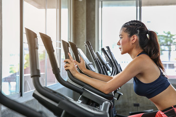 The female is cycling in the gym. Portrait of girl exercising on cardio machines in the sport club. Pretty women body builder working out at the gym. asian people.