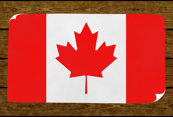 Illustration of a Canadian flag painted on the papier pasted on the woody wall