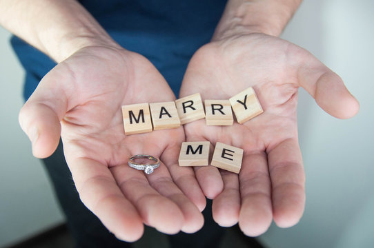 Alphabet letter wooden blocks tiles with words Marry me in man hands. Marriage proposal and love concept for Valentine`s day with wedding or engagement ring with brilliant