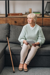 upset retired woman with blonde hair holding photos while sitting on sofa in living room