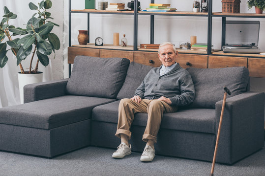senior man with grey hair sitting on sofa in living room