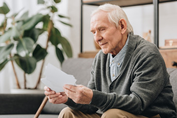 happy pensioner with grey hair looking at photos in living room