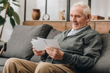 happy senior man with grey hair lookinf at photos and sitting on sofa