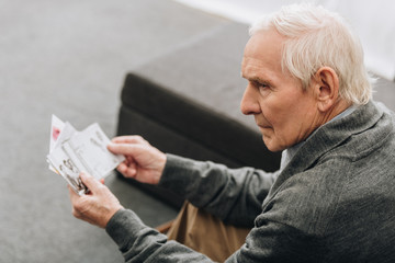 sad retired man with grey hair looking at old photos at home