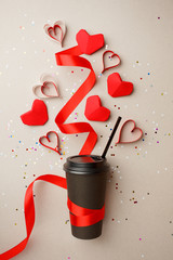 Paper Coffee Cup decorated with Red origami Heart, silk ribbon and confetti, love take away coffee and valentine day concept, copy space