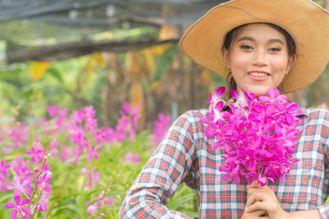 A woman gardener wearing a plaid shirt wearing a hat is holding a pink orchid in his hand. And was smiling happily. In the orchid garden
