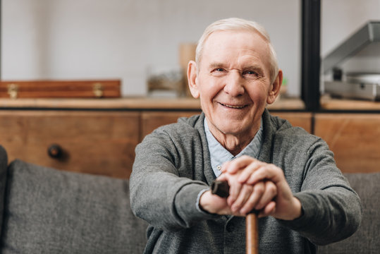 cheerful pensioner smiling and holding walking cane at home