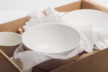 In de dag Klaar gerecht Clean white dishes in paper packed in a cardboard box. Concept relocation