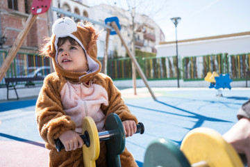 Little kid with bear or lion costume playing in playground park