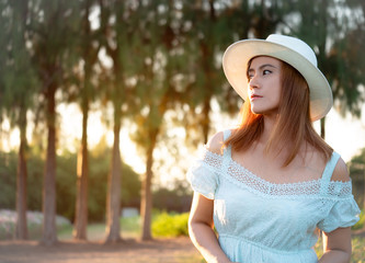 Portrait fashion ,Beautiful woman wearing white dress and hat posing at the flower parks.