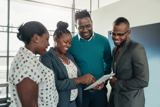 Team of african business people standing and smiling and laughing while using a tablet