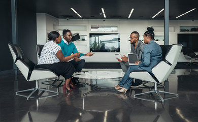 Team of african bussines people sitting in a modern office and talking during an work meeting