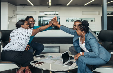 Obraz Friendly successful all african business team give high five together in office, excited happy employees celebrating corporate victory, african workers teambuilding concept - fototapety do salonu