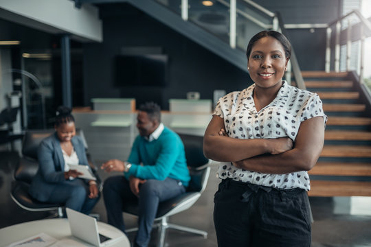 Portrait of a confident black businesswoman smiling with her arms crossed and all african team in the background