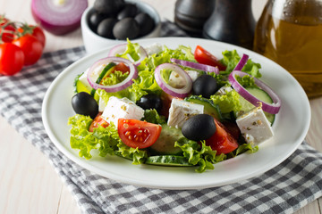Fresh Greek salad with delicious  ruccola, spinach, cabbage, arugula, feta cheese, red onion and cherry tomato on wooden background. Oil, salt and pepper. Healthy and diet food concept.