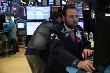 A trader looks at price monitors as he works on the floor at the New York Stock Exchange (NYSE) in New York City, New York