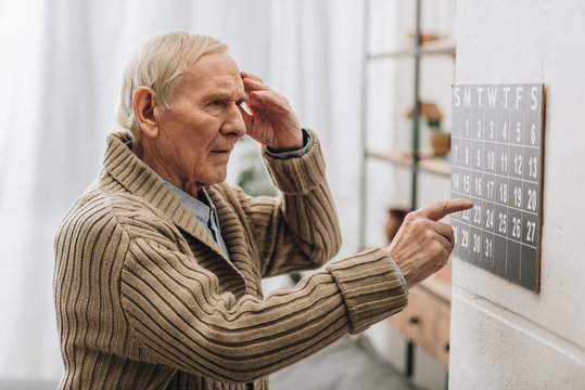 old man looking at calendar and touching head