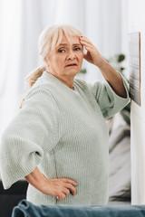 Wall Mural - upset senior woman standing near calendar on wall and holding head