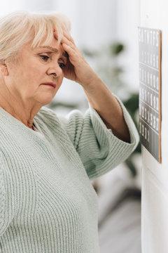 upset senior woman looking at calendar on wall