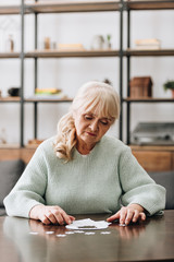 Wall Mural - retired woman looking at puzzle pieces on table